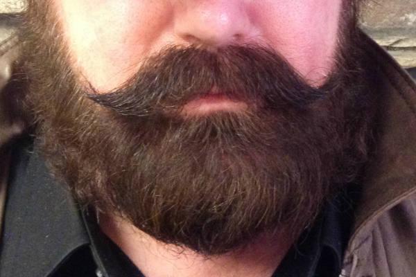 Parler dans sa barbe
